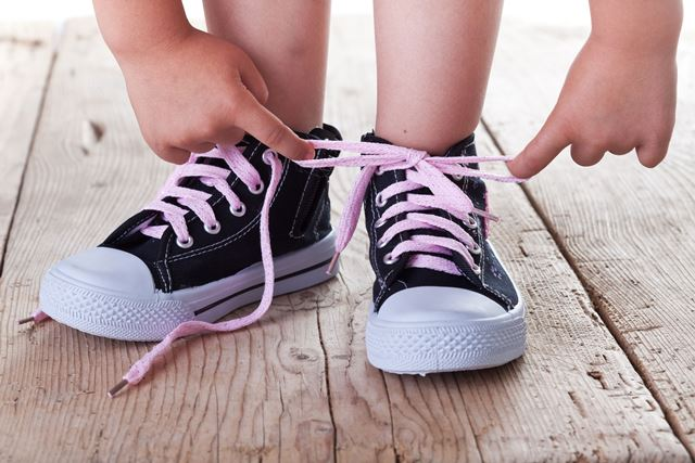 14258141 - child successfully ties shoes - closeup on feet and hands
